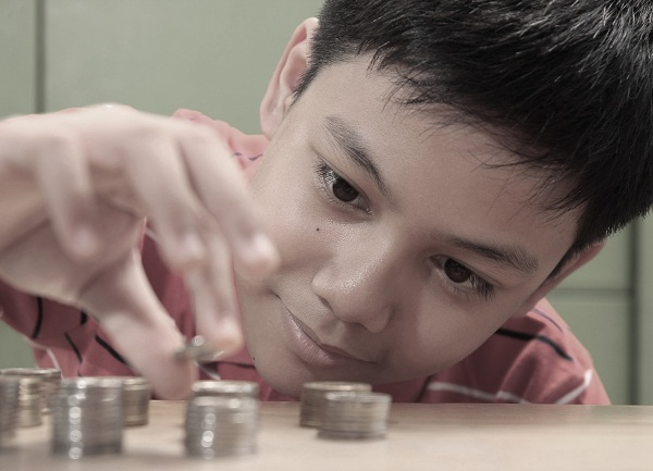 Boy Stacking a Pile of Coins